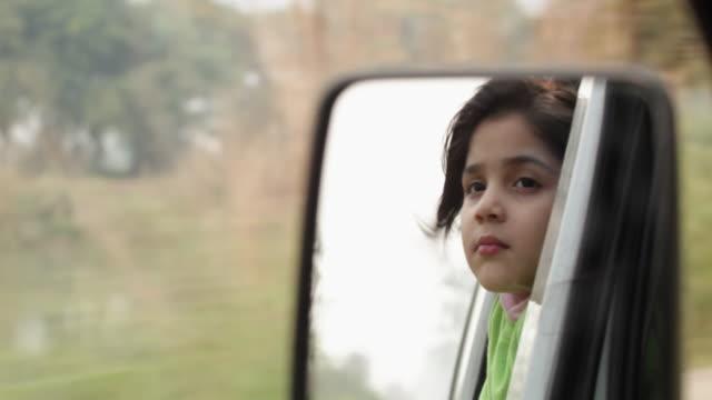 vídeos y material grabado en eventos de stock de reflection of a girl watching from window of a car  - indian ethnicity
