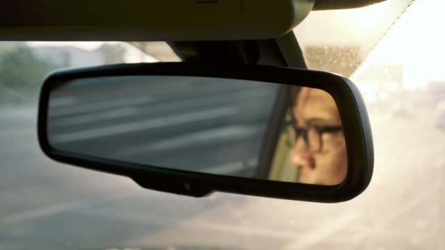 Reflection of asian man face in rear-view mirror in moving car, traffic