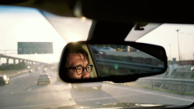 reflection of asian man face in rear-view mirror in moving car, traffic - rear view mirror stock videos and b-roll footage
