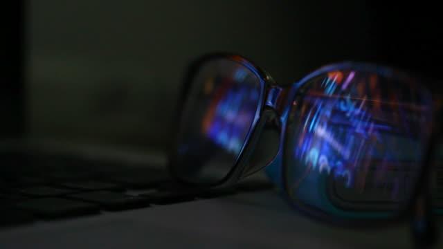 vidéos et rushes de réflexion des lunettes sur l'ordinateur portatif la nuit - verre optique