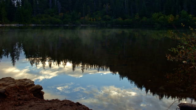Reflection of forest and mist at sunrise on Mirror Lake