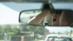 SLOW MOTION: Reflection of frustrated young man yelling at car in front of him.