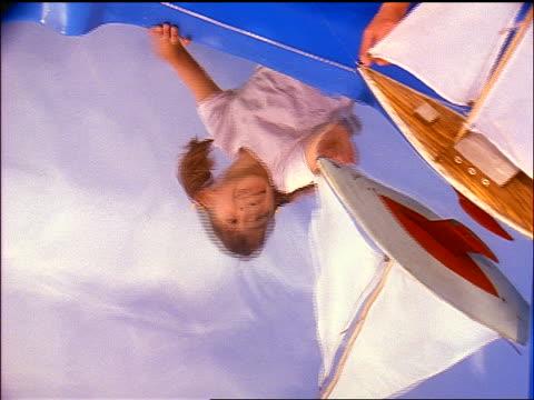 reflection of girl playing with toy sailboat in water - endast flickor bildbanksvideor och videomaterial från bakom kulisserna