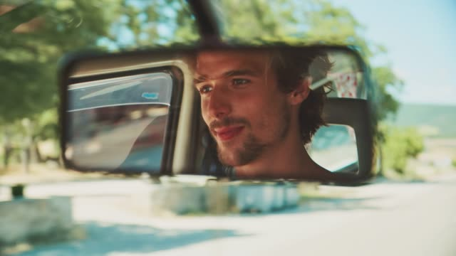 reflection of man enjoying road trip in van - mirror stock videos & royalty-free footage