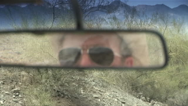 CU Reflection of man in straw hat and sunglasses in rear view mirror while driving down desert road/ Scottsdale, Arizona
