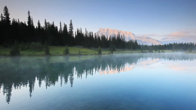 reflection of  mount rundle on lake, banff national park - rock face stock videos & royalty-free footage