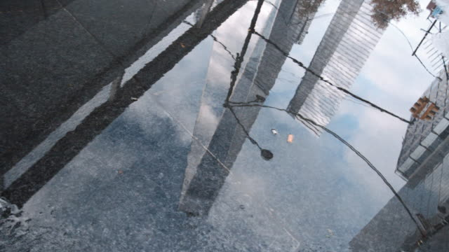 a reflection of new york city's world trade center in a sidewalk puddle - puddle stock videos & royalty-free footage