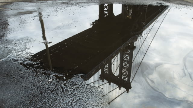 vídeos de stock e filmes b-roll de a reflection of nyc's manhattan bridge in a puddle on a gloomy spring day - 4k - poça