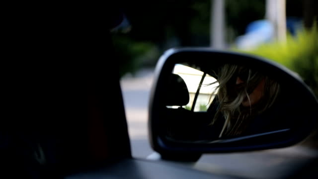 Reflection of pretty woman from car side mirror