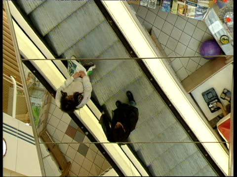 Reflection of shoppers using escalator on mirrored wall of shopping mall Kingston upon Hull