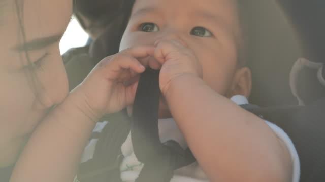 reflexion der sonne während mutter küssen, um baby sohn. aktive eltern und menschen outdoor-aktivität in den sommerferien mit kindern. frohe familienurlaube. urlaub - east asian ethnicity stock-videos und b-roll-filmmaterial