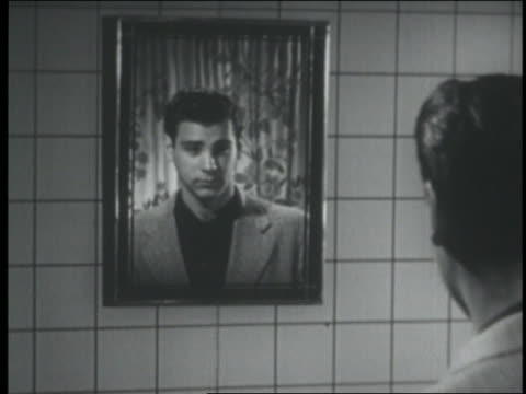 B/W 1951 REAR VIEW reflection of teen boy combing hair in mirror + smiling