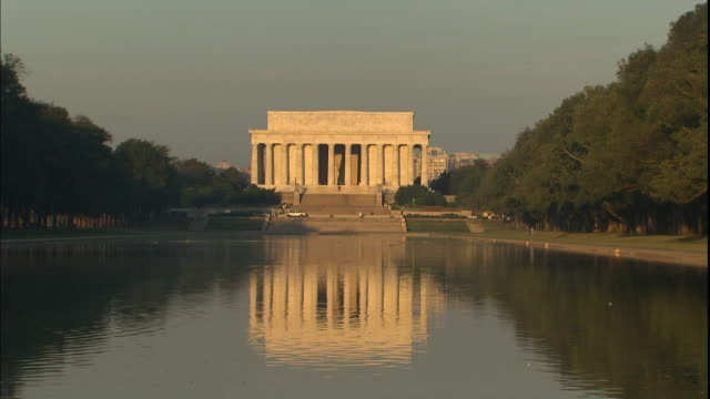 vidéos et rushes de a reflection of the lincoln memorial ripples in a reflecting pool. - lincoln memorial