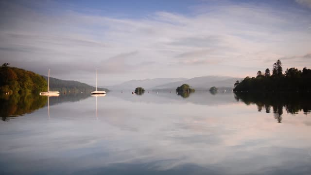reflection of the sky on the clear waters of the lake surrounded by green forest and mountains in lake district, england. -wide shot - anchored stock videos & royalty-free footage