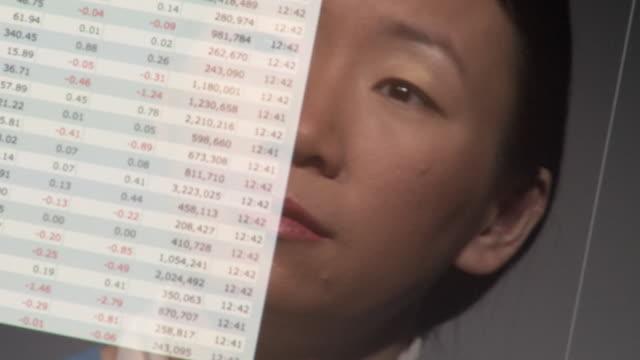 ECU R/F Reflection of woman examining screen with scrolling numeric data / Atlanta, Georgia, USA