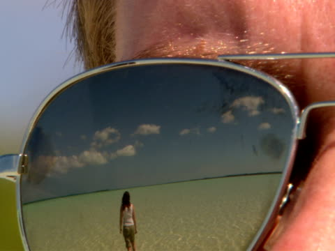 CU,  reflection of woman walking in shallow water in men's sunglasses
