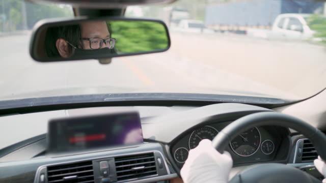 vídeos y material grabado en eventos de stock de reflexión sobre el taxista que usa máscara protectora para la cara y guante de plástico mientras conduce - taxista