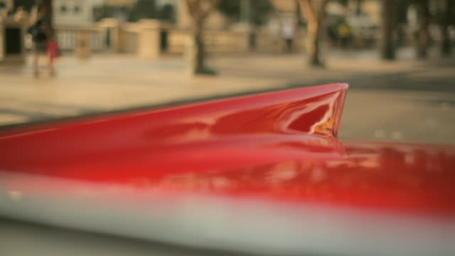 vídeos y material grabado en eventos de stock de reflections flash in the back fin of a red vintage automobile as it cruises down a city street. - pasear en coche sin destino