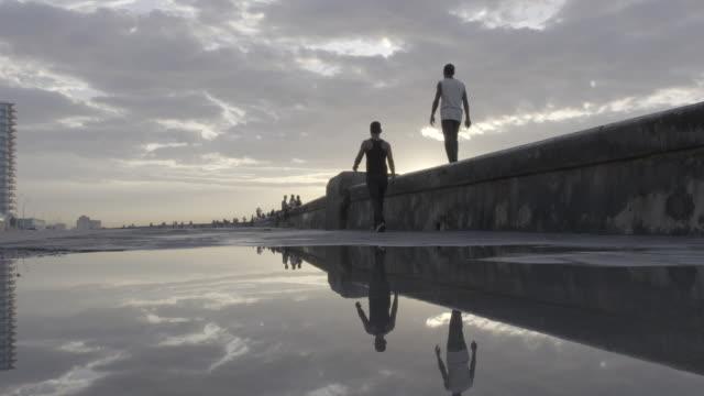 Reflections in water of men walking along pier wall