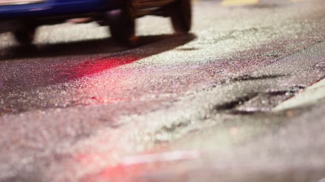 vidéos et rushes de reflections of lights and silhouettes of passing cars on wet road at night - moving past