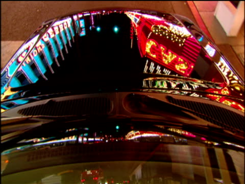 Reflections of neon lights and Vegas attractions on traveling car windscreen. Las Vegas.