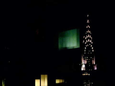 reflections on inside of windows of revolving restaurant with illuminated spire of chrysler building in background at night manhattan - tornspira bildbanksvideor och videomaterial från bakom kulisserna