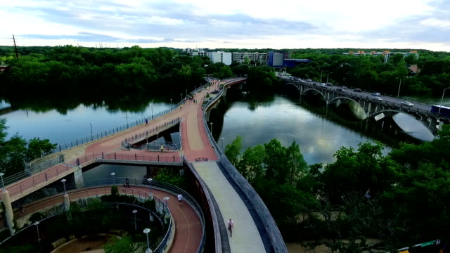 reflections on lady bird lake over pedestrian hike and bike walking bridge - footbridge stock videos & royalty-free footage