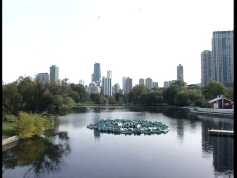 Reflective lake sprinkler system middle reflecting trees all around in zoo Chicago cityscape BG No animals IL