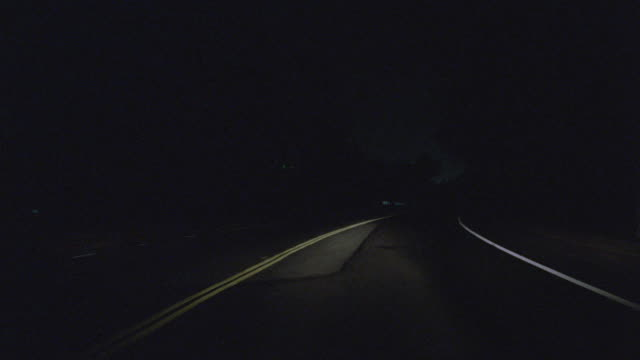 reflective lines guide vehicles along a darkened highway. - fanale anteriore video stock e b–roll