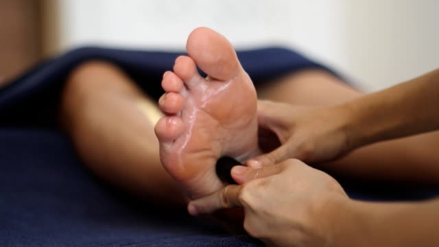 reflexology foot massage, spa foot treatment by wood stick,thailand - reflexology stock videos and b-roll footage