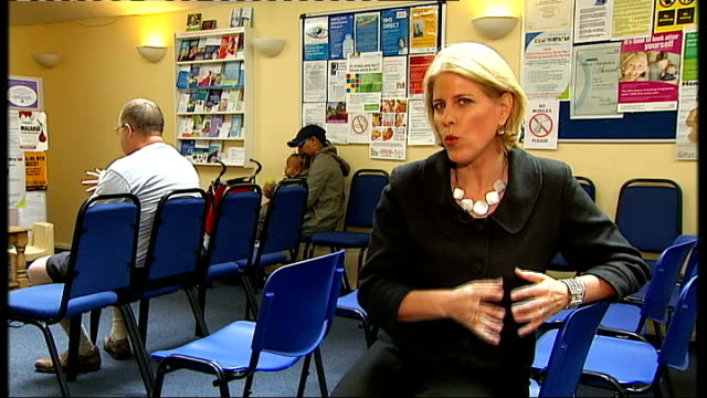 NHS Future Forum Team call for significant changes Back views of patients seated in GP surgery waiting room Reporter to camera