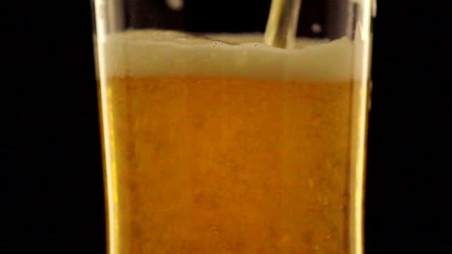 vídeos de stock, filmes e b-roll de refrescante cerveja de vidro escuro a girar na noite - enchendo