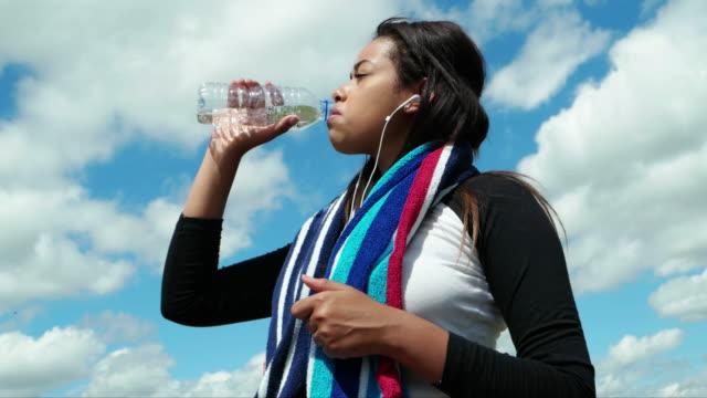 stockvideo's en b-roll-footage met verfrissende water. drinken uit een fles. - in een handdoek gewikkeld