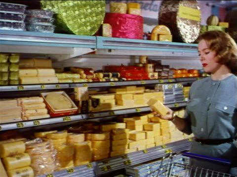 1962 PAN of refrigerated cheese section of grocery store to woman looking at cheese / industrial