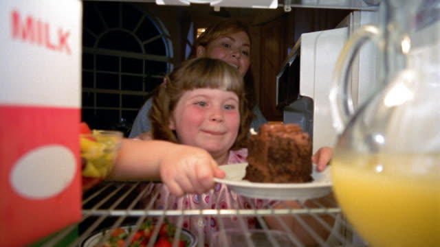 Refrigerator point of view girl taking chocolate cake with woman denying her and giving her bowl of fruit