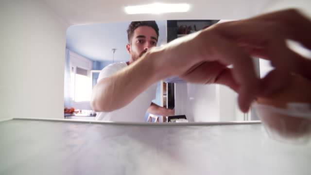 pov refrigerator young man taking an egg - refrigerator stock videos and b-roll footage