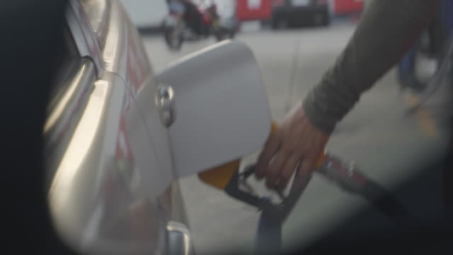 refueling car at gas station pump through the car side mirror - fuel pump stock videos & royalty-free footage