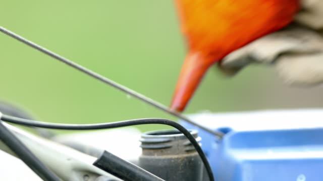 refuelling the tank of a lawn mower. - trädgårdshandske bildbanksvideor och videomaterial från bakom kulisserna
