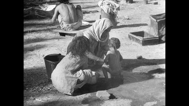vídeos de stock e filmes b-roll de refugee camp refugees elder woman w/ reclined man woman trying to cook bathing toddler child in bucket water vs refugees boarding train older man... - 1947