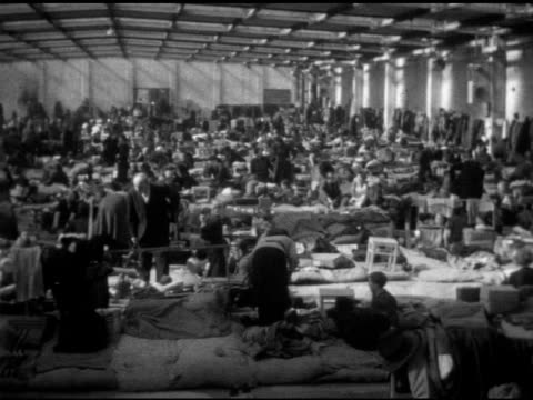 refugee camp warehouse int vs east berlin refugees crowded together in skylight warehouse floor various men women children families women changing... - flüchtlingslager stock-videos und b-roll-filmmaterial