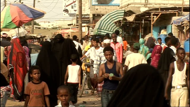 Sun rising over city People along in crowded area and man with headscarf looking at camera Young girl on father's shoulders