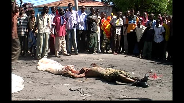 refugee crisis following renewed fighting; mob surrounding corpse of ethiopian soldier killed after being dragged naked through street - somalia stock videos & royalty-free footage