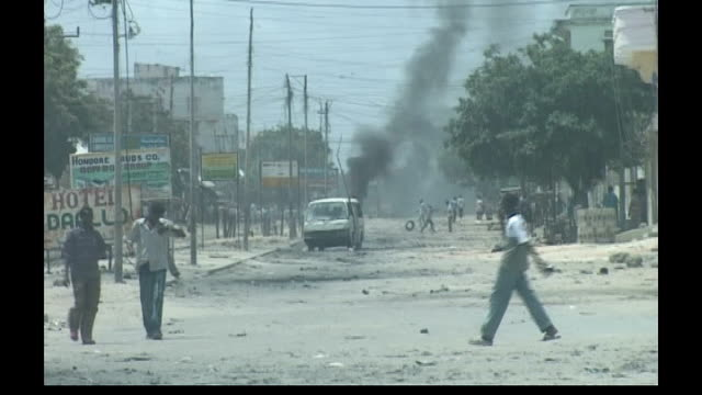 Refugee crisis following renewed fighting Mogadishu EXT People along past burning tyres on streets Man covering corpse with blanket