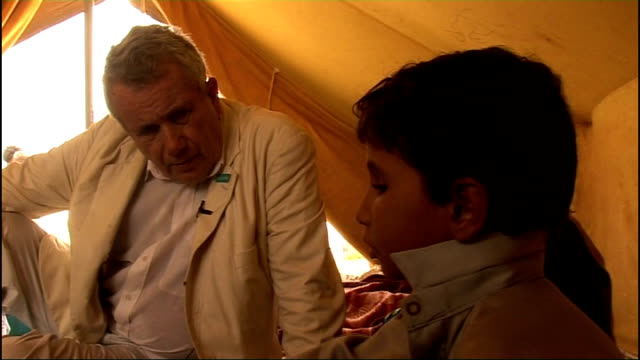 Refugee crisis INT Six year old boy Abbas talking to reporter and showing injuries received from landmine on chest SOT