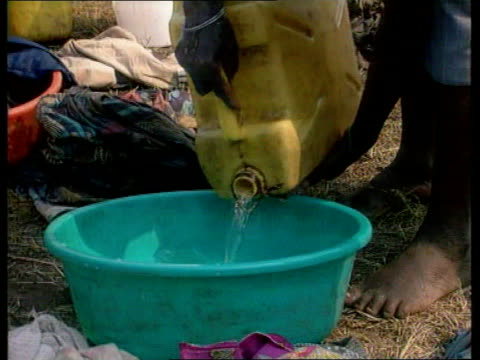 Relief GV Women shake out blankets and perform domestic work CMS Water pours from plastic petrol can into plastic basin TGV Refugee camp as fires...