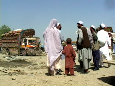 vidéos et rushes de ws refugee family and trucks, shitral valley, north west province, pakistan - pakistan