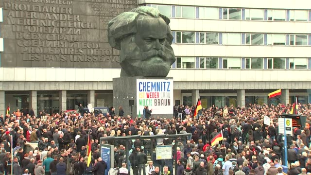 refugee protests in chemnitz; germany: saxony: chemnitz: brückenstraße: ext anti-refugee protesters with german flags / riot police / karl marx... - saxony stock videos & royalty-free footage