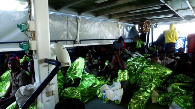 refugees and migrants are seen on board the migrant offshore aid station 'phoenix' vessel after being rescued at sea on may 19, 2017 in trapani,... - mediterranean sea stock videos & royalty-free footage