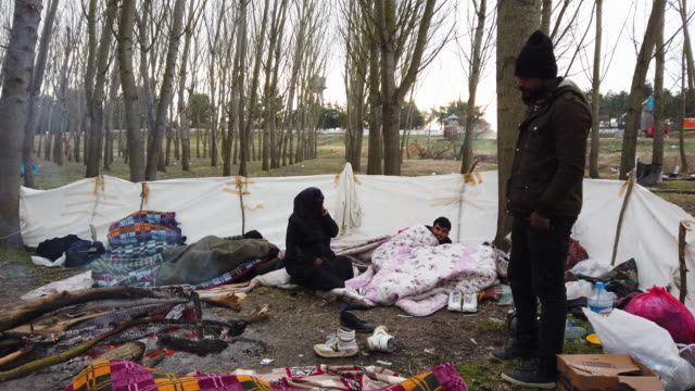refugees and migrants rest at a camp site where refugees and migrants from various countries wait on the turkish shoreline of the evros river to... - flüchtlingslager stock-videos und b-roll-filmmaterial