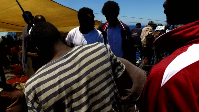 refugees and migrants rest on board the migrant offshore aid station 'phoenix' vessel on may 25 2017 off lampedusa italy the crew of the 'phoenix'... - 難民点の映像素材/bロール